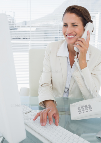 Smiling businesswoman using computer and phoneの素材 [FYI00000008]