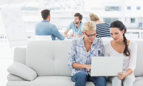 Women using laptop with colleagues in background at creative officeの素材 [FYI00000021]