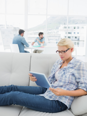 Woman using digital tablet with colleagues in background at creative officeの素材 [FYI00000022]