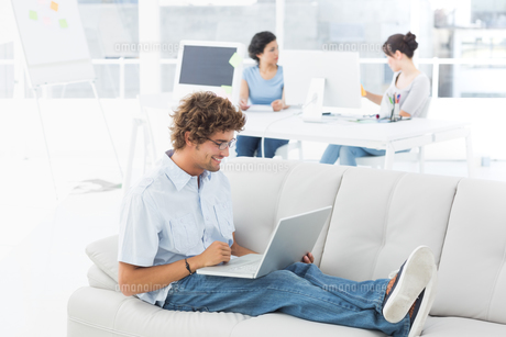Man using laptop with colleagues at creative officeの素材 [FYI00000048]