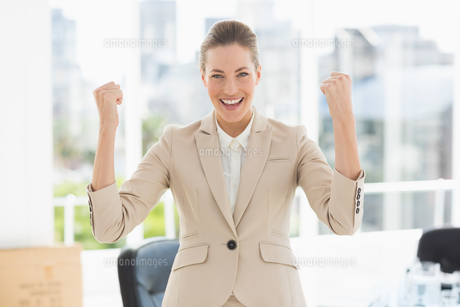 Cheerful businesswoman clenching fists in officeの素材 [FYI00000063]