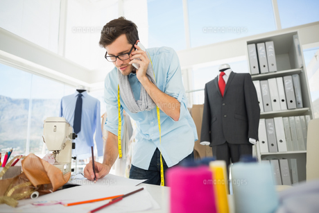 Fashion designer working on his designs while on callの素材 [FYI00000083]
