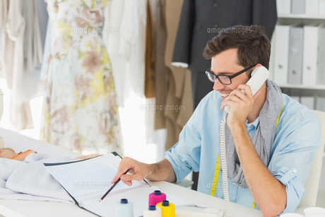 Smiling male fashion designer using phone in the studioの素材 [FYI00000085]