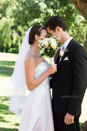 Loving couple kissing behind bouquet in gardenの素材 [FYI00000695]