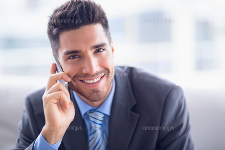 Handsome businessman sitting on sofa making a call smiling at cameraの素材 [FYI00000903]
