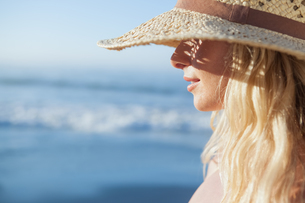 Gorgeous blonde in straw hat smiling on beachの素材 [FYI00002063]