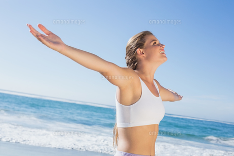 Sporty blonde standing on the beach with arms outの素材 [FYI00002142]