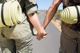 Hitch hiking couple standing holding hands on the roadの素材 [FYI00002466]