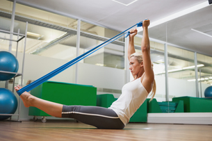 Side view of woman using resistance band in fitness studioの素材 [FYI00002905]