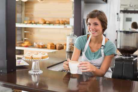 Pretty barista offering cup of coffee smilingの素材 [FYI00003326]