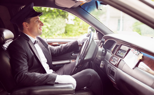 Limousine driver driving and smilingの素材 [FYI00003512]