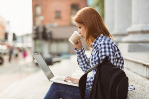 Woman drinking coffee and using laptop outsideの素材 [FYI00003865]