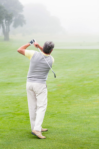 Golfer swinging his club on the courseの素材 [FYI00006037]
