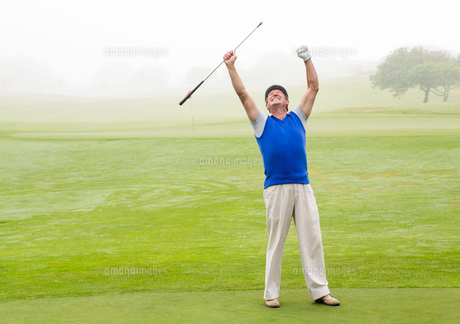 Excited golfer cheering on putting greenの素材 [FYI00006038]