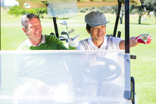 Golfing friends driving in their golf buggyの素材 [FYI00006097]