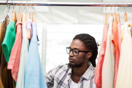 Male fashion designer looking at rack of clothesの素材 [FYI00006123]