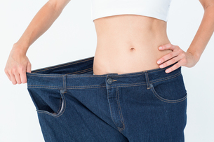Slim woman wearing too big jeansの素材 [FYI00006622]