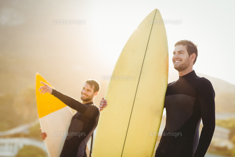 Two men in wetsuits with a surfboard on a sunny dayの素材 [FYI00007100]