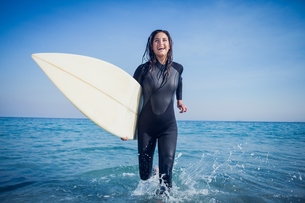 woman in wetsuit with a surfboard on a sunny dayの素材 [FYI00007121]