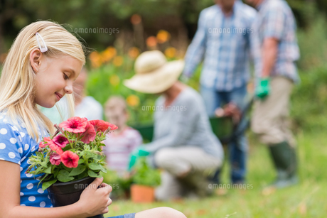 Young girl sitting with flower potの素材 [FYI00007391]