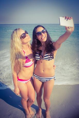 two friends in swimsuits taking a selfieの素材 [FYI00007850]