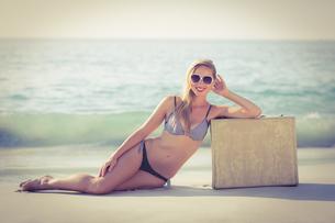 Stylish blonde leaning on suitcase on the beachの素材 [FYI00007871]