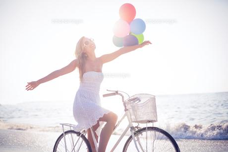 Beautiful blonde on bike ride holding balloonsの素材 [FYI00007874]