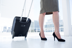 Businesswoman pulling her suitcase in the officeの素材 [FYI00008332]
