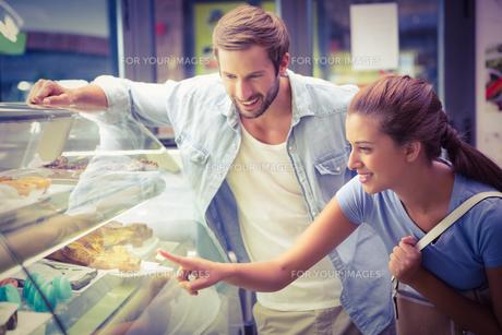 Young happy couple choosing cakeの素材 [FYI00009197]