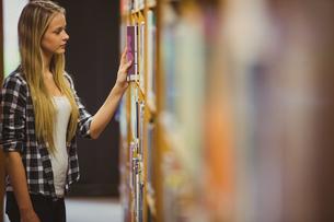 Blonde student reading book next to bookshelfの素材 [FYI00010298]
