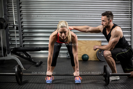 Trainer helping woman with lifting barbellの素材 [FYI00010485]
