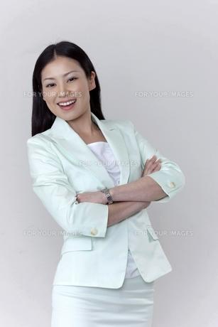 笑顔で腕組みをするビジネスウーマンの素材 [FYI00119637]