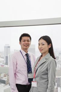 窓辺に立つビジネスマンとビジネスウーマンの素材 [FYI00119651]