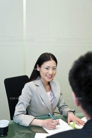 笑顔で上司と話しをするビジネスウーマンの素材 [FYI00119668]