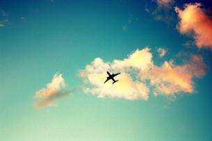 夕焼けの空へと飛び立つ飛行機の素材 [FYI00180883]