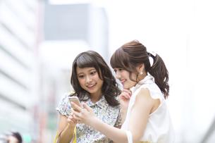 街中でスマートフォンを見る女性2人の素材 [FYI00465728]