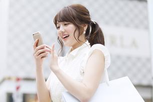 街中でスマートフォンを操作する女性の素材 [FYI00465729]