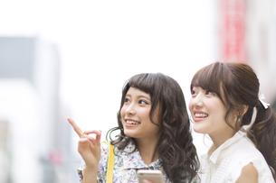 街中でスマートフォンを持ち微笑む女性2人の素材 [FYI00465730]