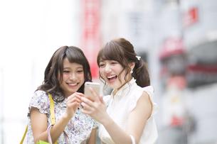街中でスマートフォンを見る女性2人の素材 [FYI00465733]