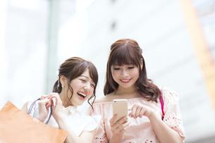 街中でスマートフォンを持ち笑う女性2人の素材 [FYI00465734]