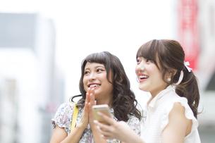 街中でスマートフォンを持ち笑う女性2人の素材 [FYI00465735]