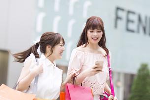 街中でスマートフォンを持ち笑う女性2人の素材 [FYI00465737]