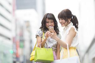 街中でスマートフォンを見る女性2人の素材 [FYI00465741]