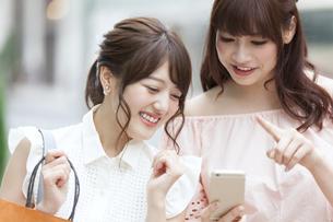 街中でスマートフォンを持ち笑う女性2人の素材 [FYI00465743]