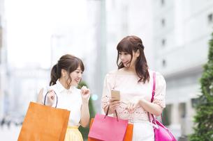 街中でスマートフォンを持ち笑う女性2人の素材 [FYI00465744]