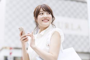 街中でスマートフォンを持ち微笑む女性の素材 [FYI00465747]