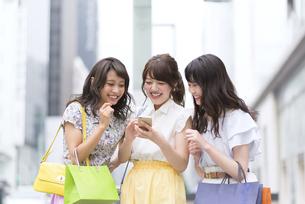 街中でスマートフォンを持ち笑う女性3人の素材 [FYI00465761]