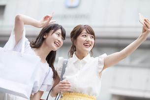 街中で写真を撮る女性2人の素材 [FYI00465768]