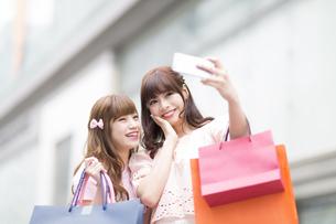 街中で写真を撮る女性2人の素材 [FYI00465771]