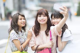 街中で写真を撮る女性3人の素材 [FYI00465774]
